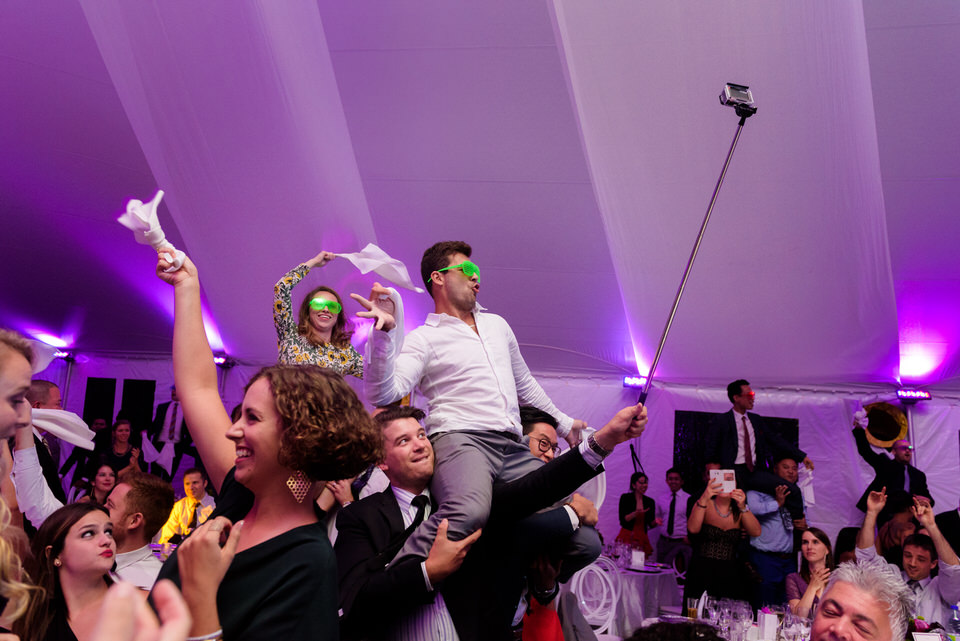 Guests dancing on chairs at wedding reception
