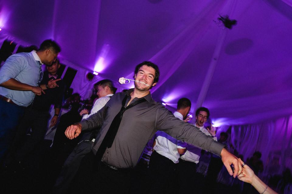 Man dancing with paper flower in his teeth