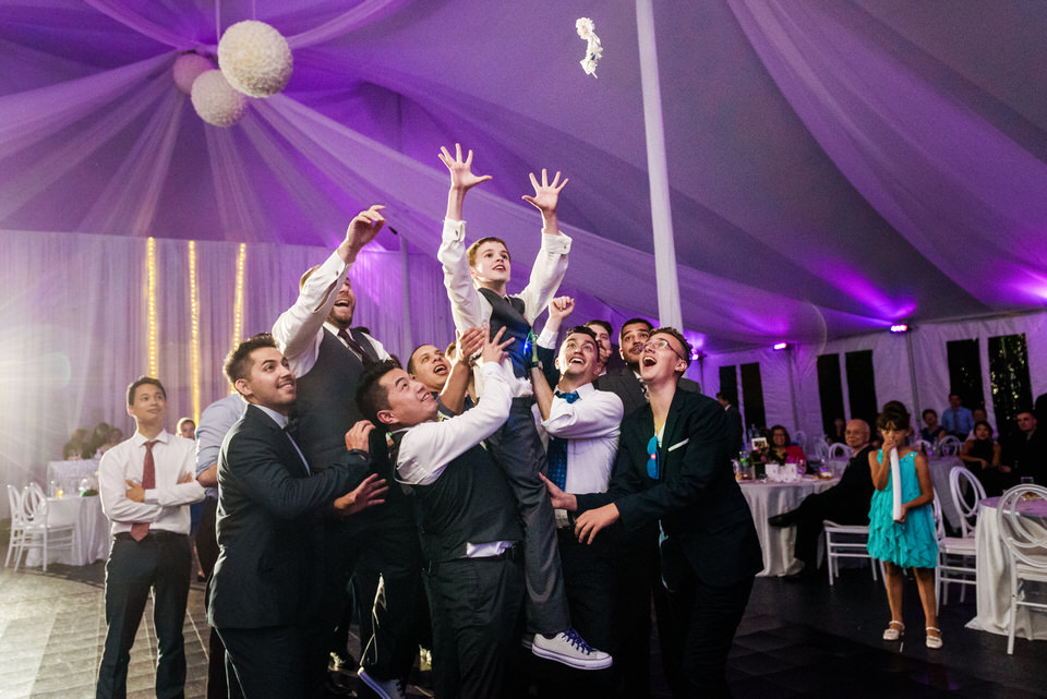 Single guys lifting a small boy to catch the garter belt