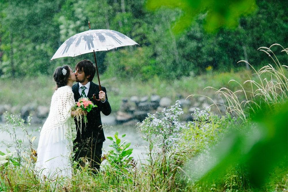 Mariés sous la pluie a cote d'un lac