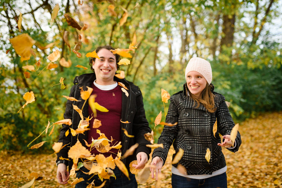 Smiling couple surrounded by autumn leaves