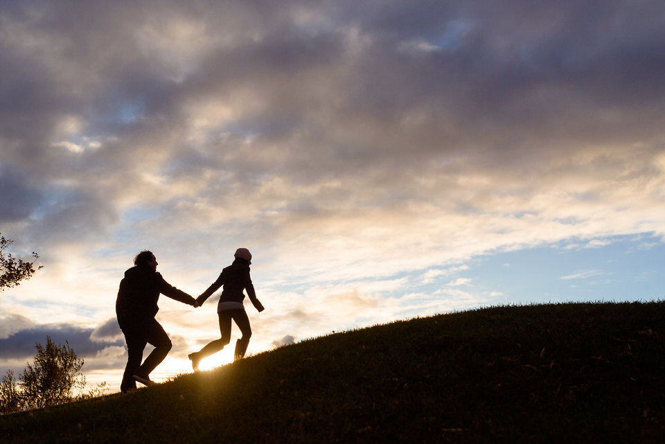 couple going up a hill during sunset