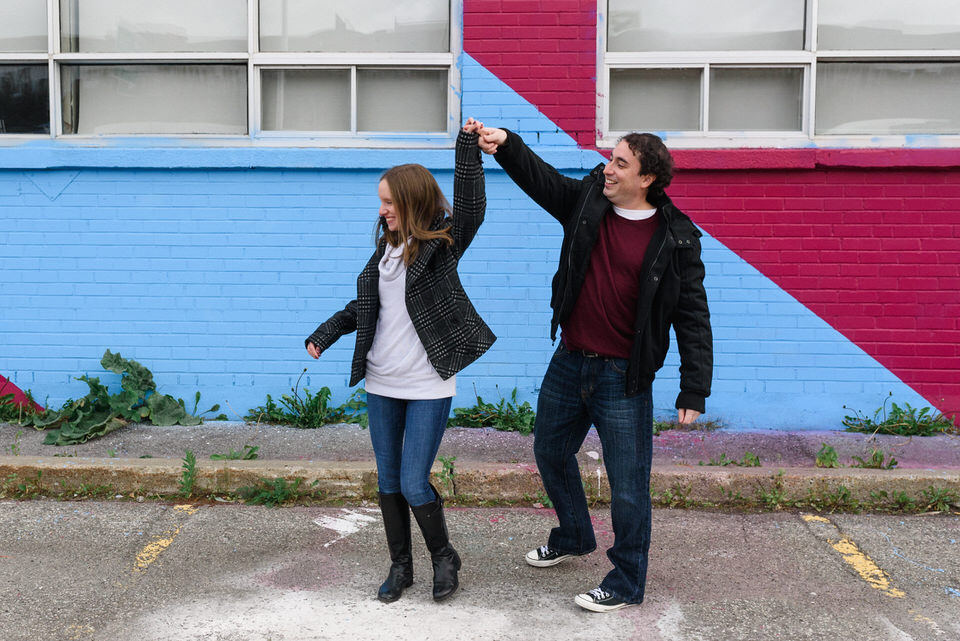 Newly engaged couple dancing in the street of Montreal in front of a graffiti mural