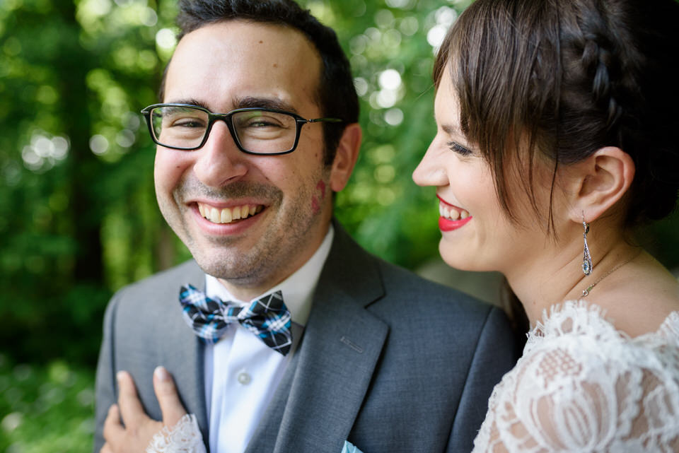 Groom laughing as bride looks at lipstick print she left on his cheek