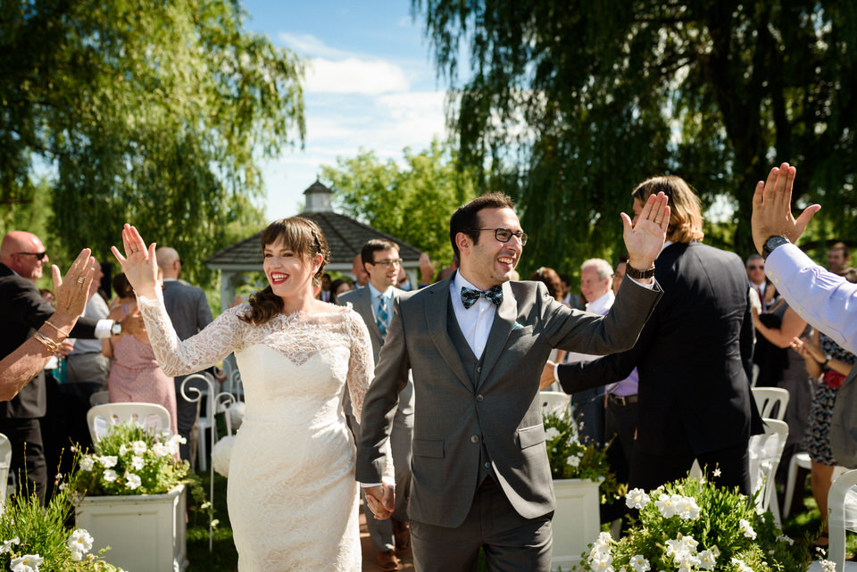 Wedding couple giving high fives to guests as they walk down the aisle