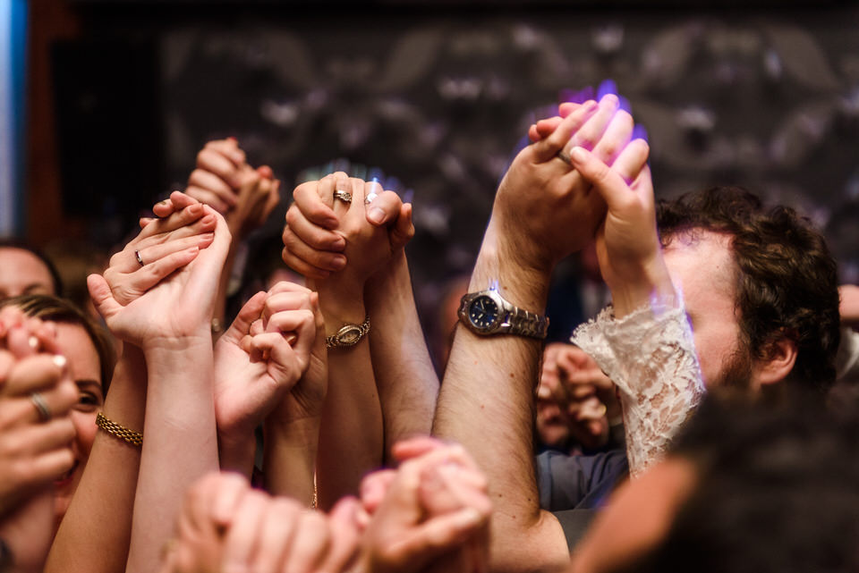 Close up of many hands clasped together during hora dance