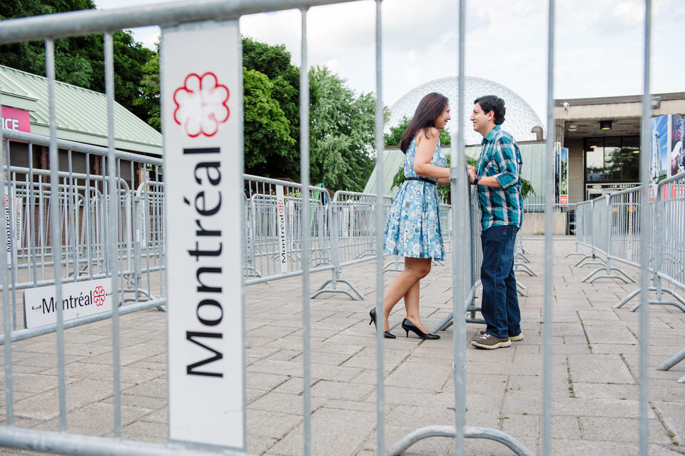 """Engaged couple leaning on railing and framed by words """"Montreal"""""""