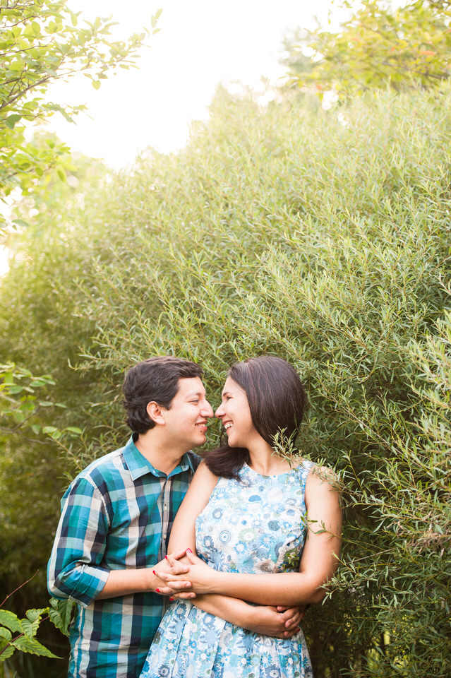 Engaged couple hugging in greenery at Jean-Drapeau Park