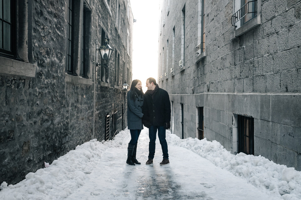 Engaged couple holding hands and looking at each other in snowy old Montreal streets
