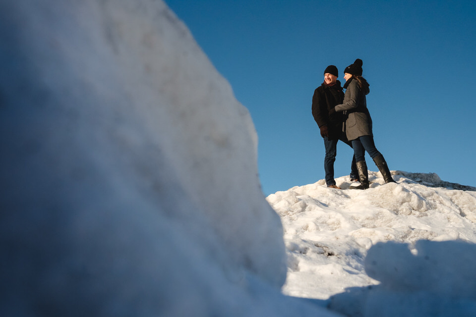 Couple posing on top of snowy mountain