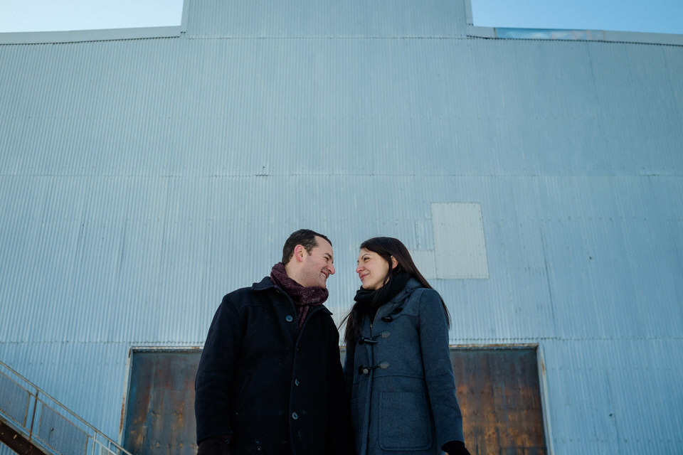 couple smiling at each other in front of an old empty warehouse door