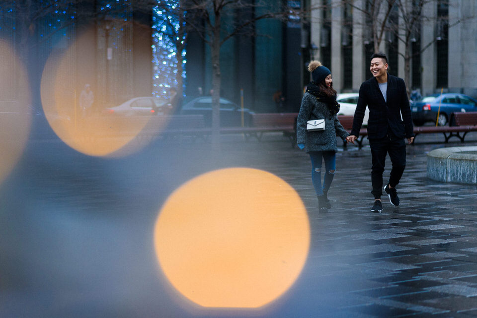 Couple walking through Place d'Armes in the rain