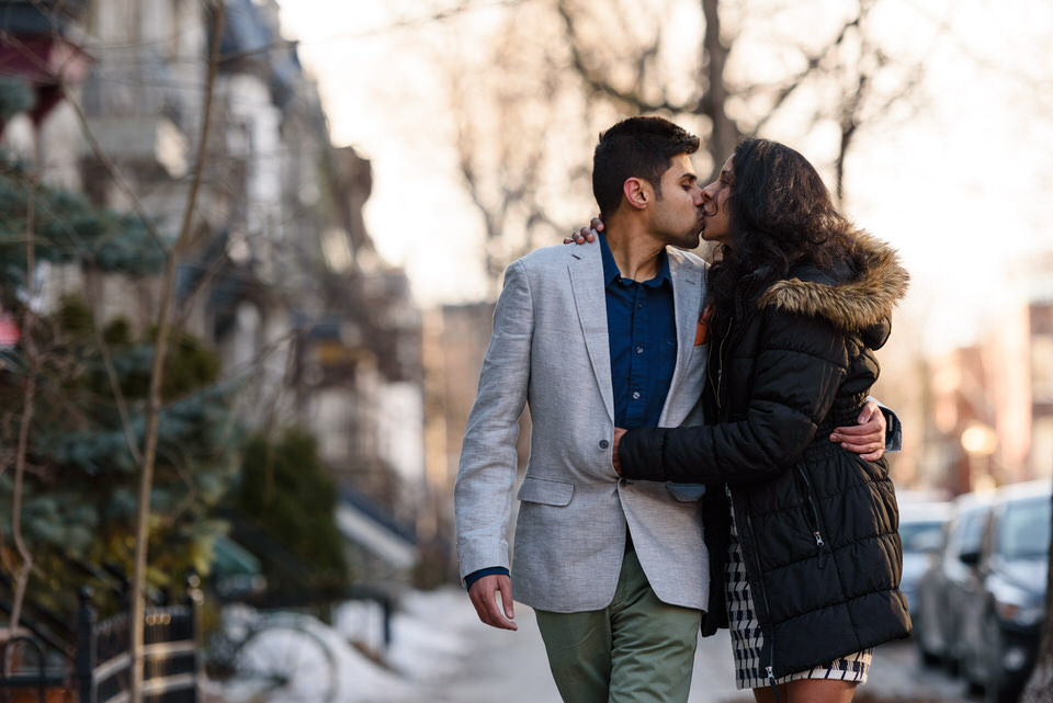 Newly engaged couple kissing on the winter street
