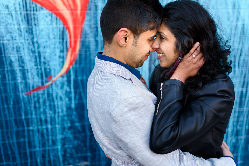 Newly engaged couple in front of graffiti mural in Montreal