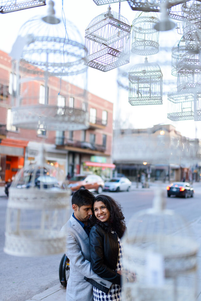 Couple hugging framed by hanging birdcages