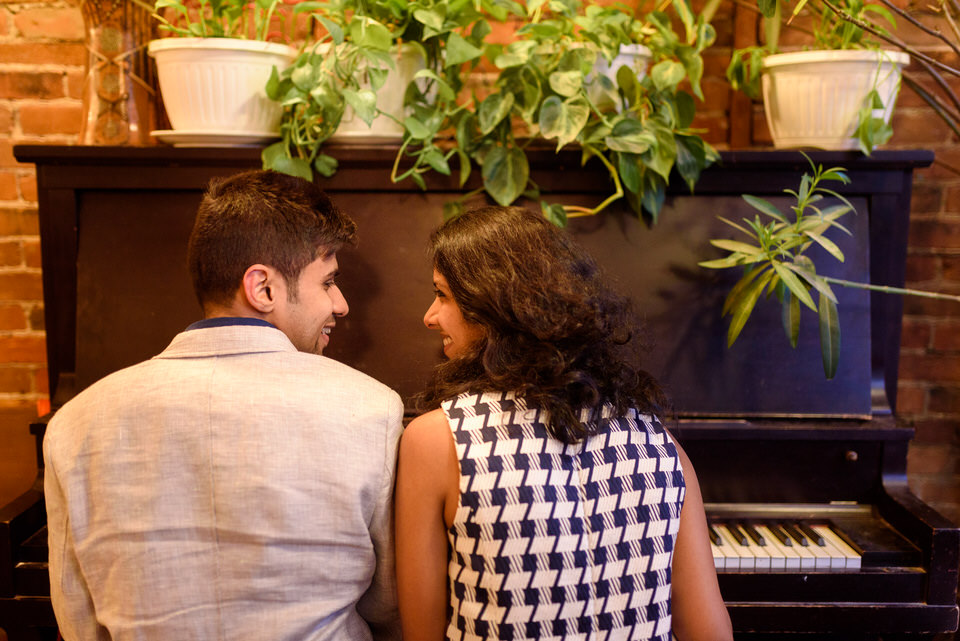 Newly engaged couple playing the piano together at Le Depanneur coffeeshop