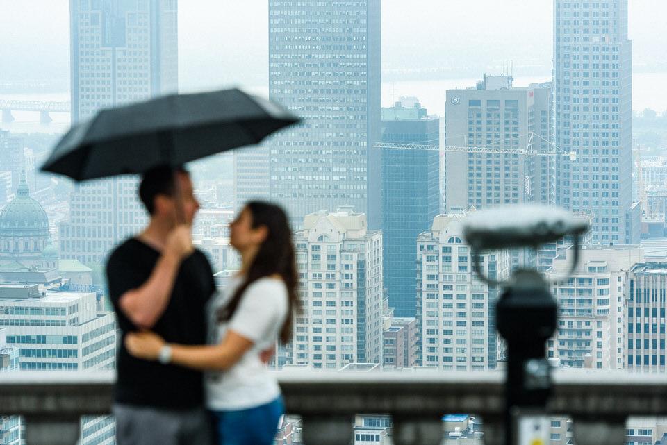 Couple under umbrella with Montreal skyline behind
