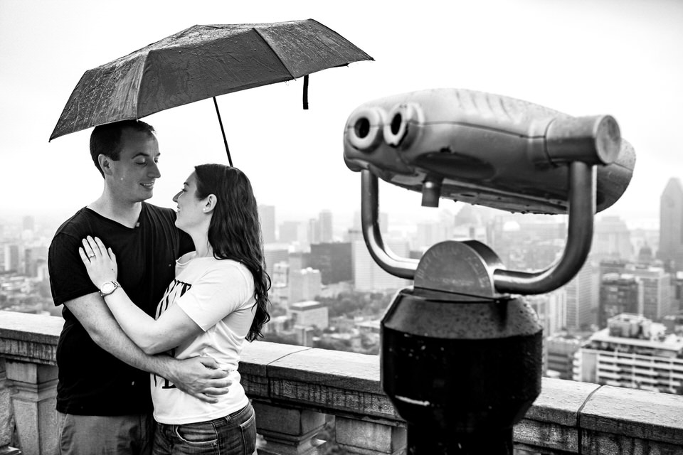 Just engaged couple in the rain under an umbrella