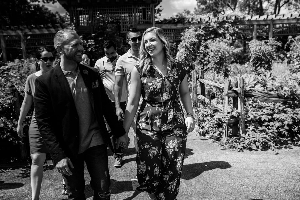 Couple holding hands walking with friends inside the botanical garden