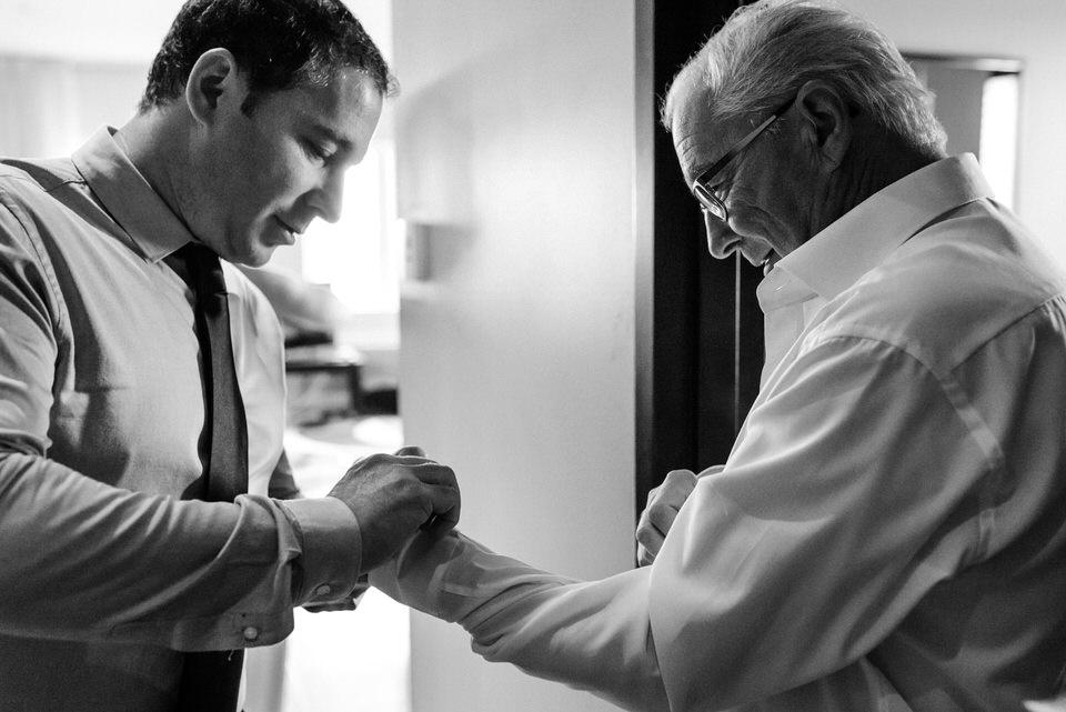 Man doing up cuffs of older man