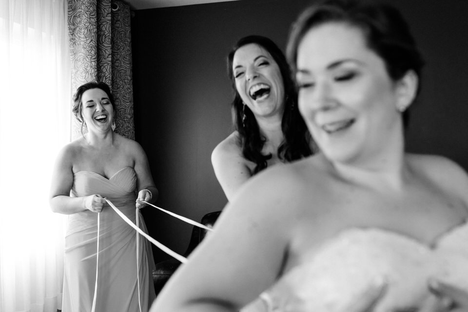 Candid photo of bridesmaids lacing up the bride's dress