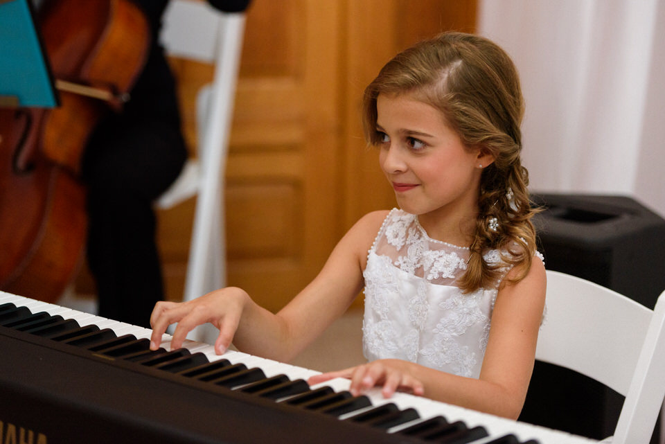 Bride's daughter playing piano at kid-friendly wedding ceremony