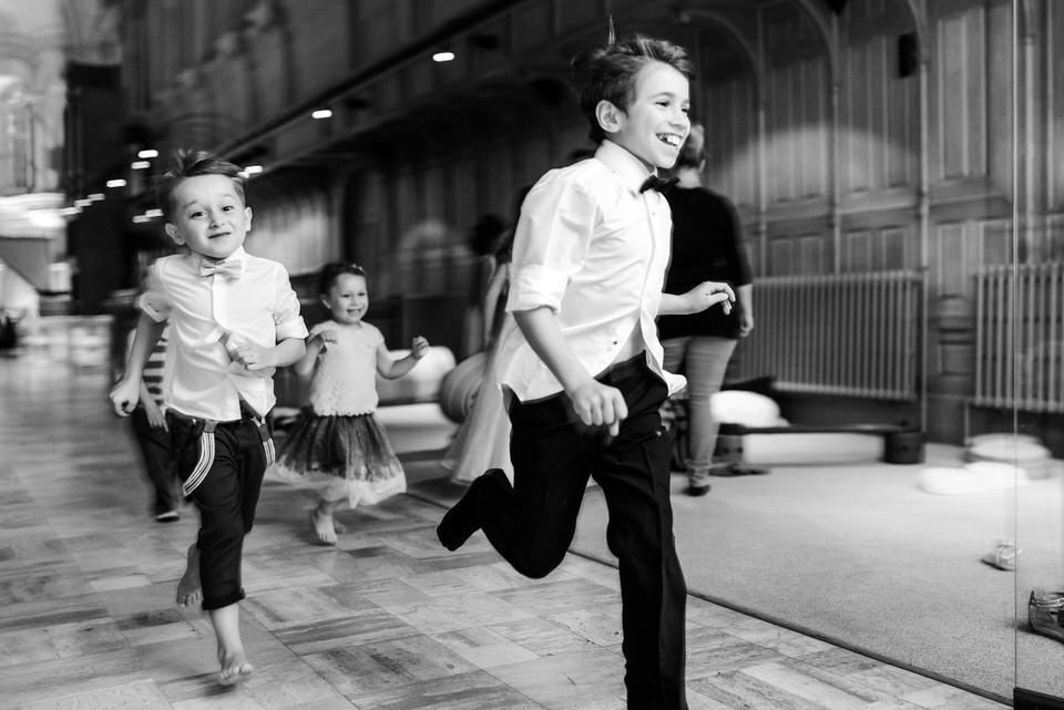 Black and white candid photo of children running at Abbaye Oka wedding