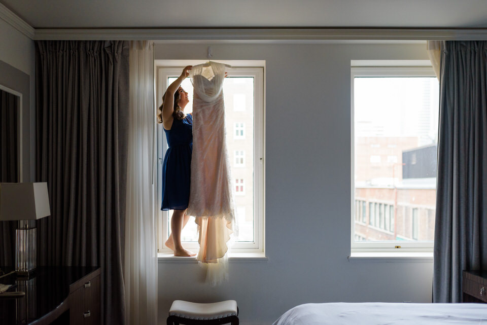 Bridesmaid hanging up wedding dress