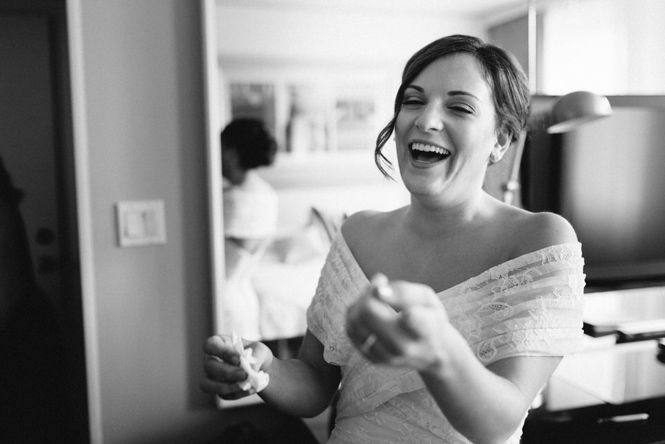 Bride laughing with friend in hotel room