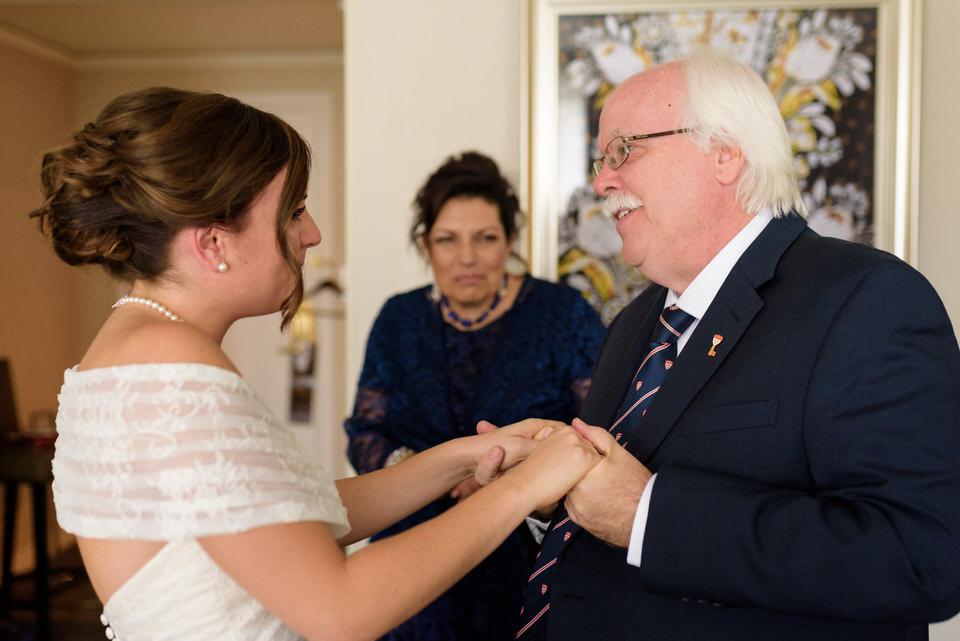 Bride's dad holding hands daughter