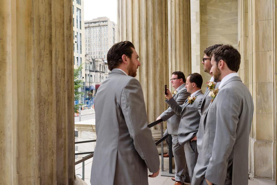 Groomsmen taking selfies in front of Montreal museum of fine arts