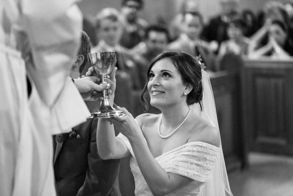 Bride kneeling in front of priest taking communion