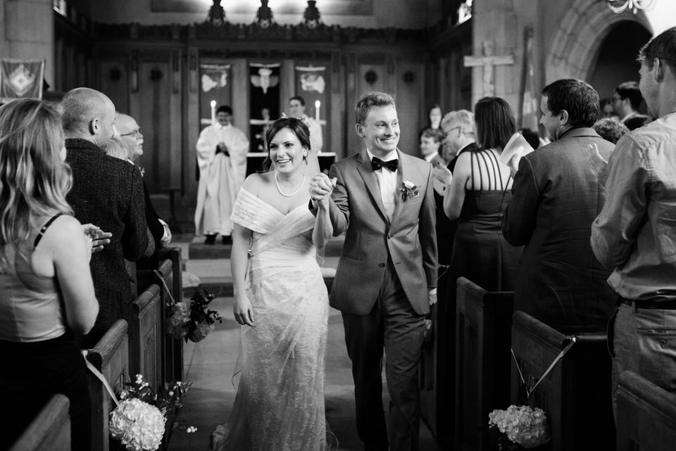 Married couple hand in hand walking back the aisle