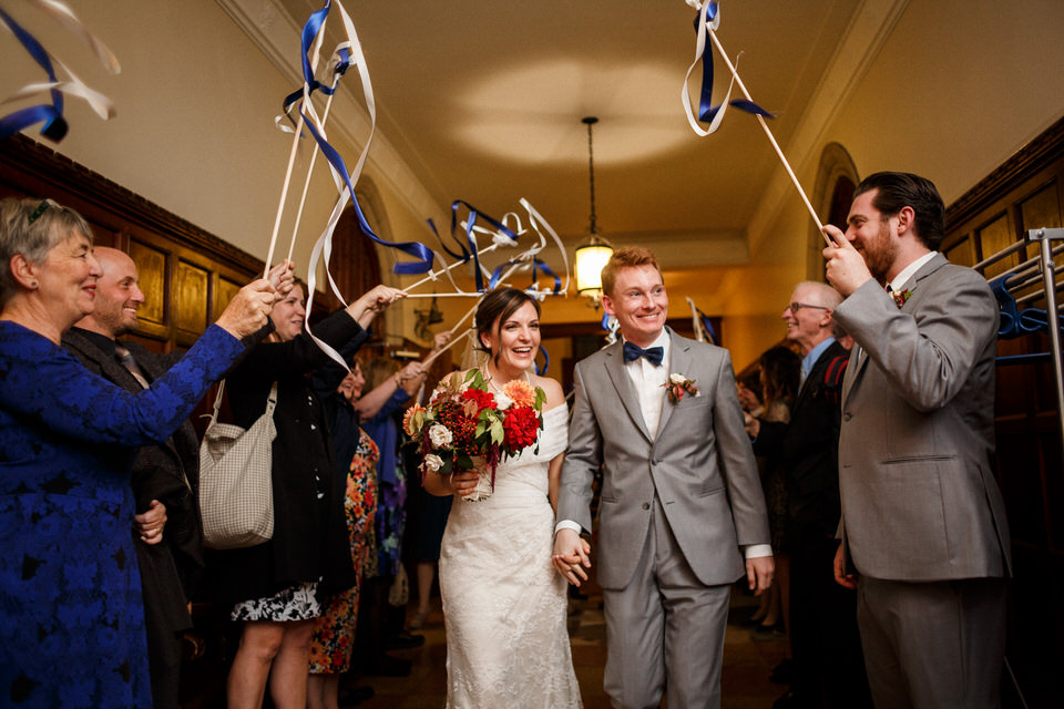 Family and friends waving ribbon stick at the married couple