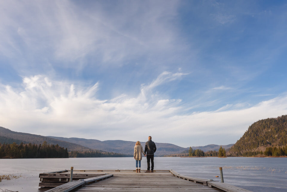 A couple holding hands seen from the back as they look over lake landscape