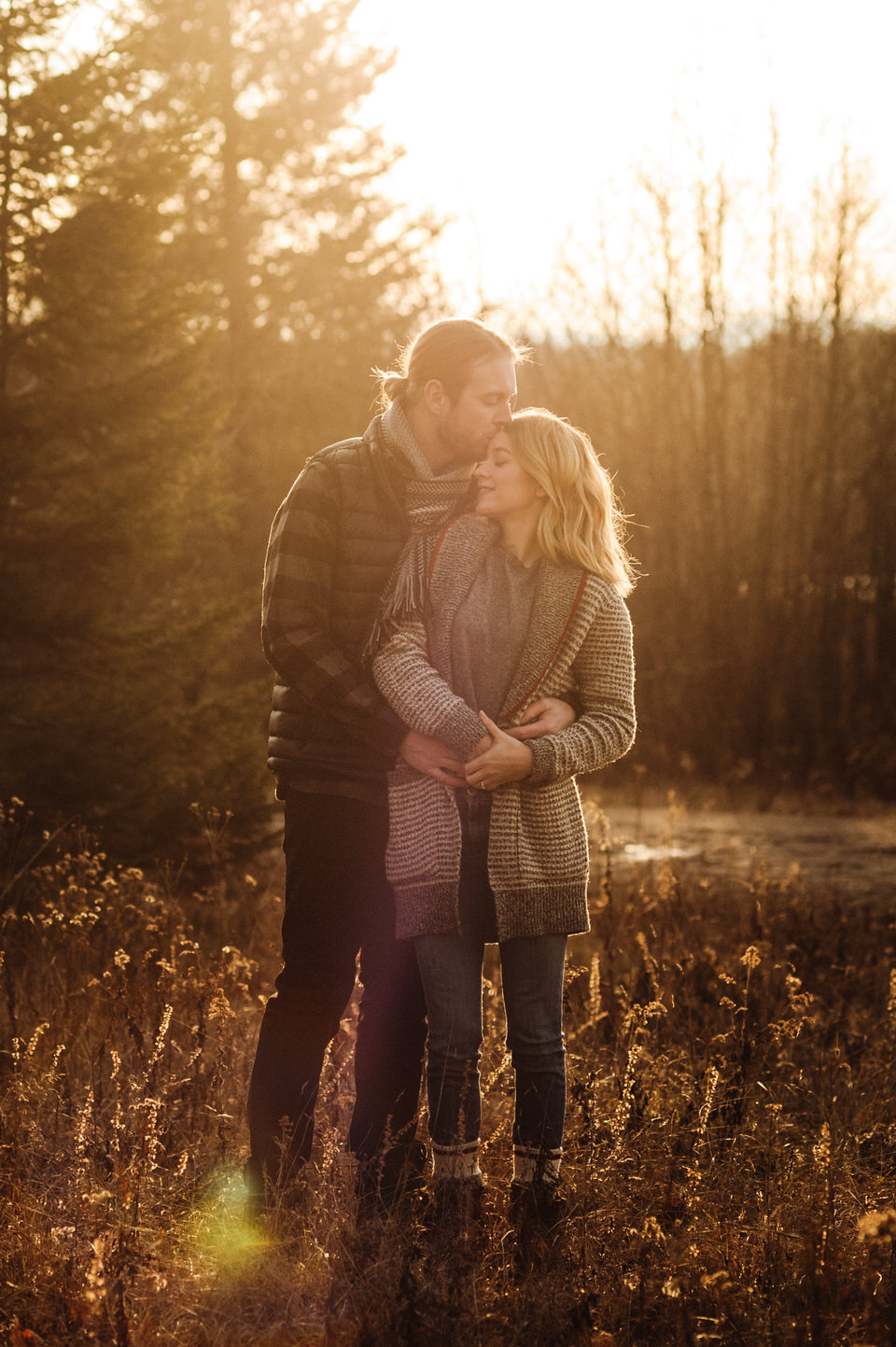 Engagement photo of couple in the woods at sunset