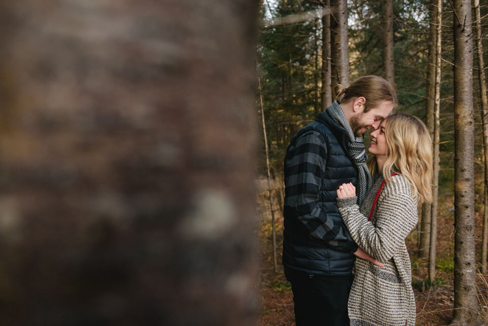 Engaged couple framed by woods and tree trunks