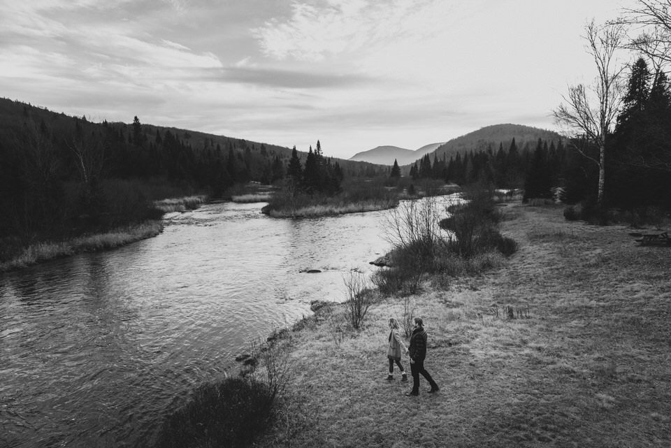 Black and white photo of couple seen from above walking toward a river
