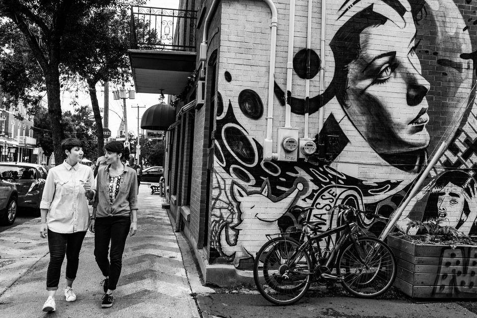 Lesbian couple walking by art mural in Montreal during engagement photo session