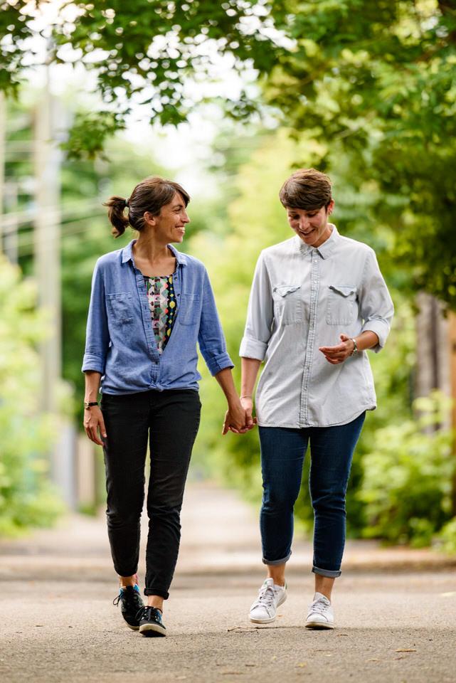 Same-sex couple walking in Montreal's green alleyways