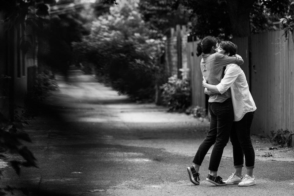 Same-sex couple hugging in Montreal's green alleyways
