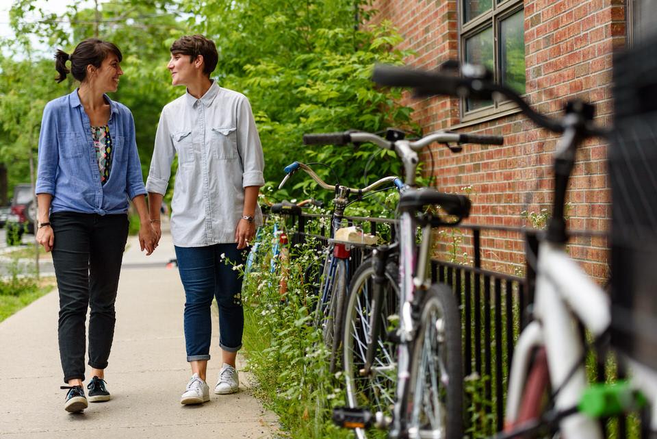 Lesbian couple walking along Montreal sidewalk near locked bikes