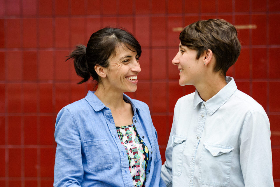 LGBT engagement photo in front of red wall