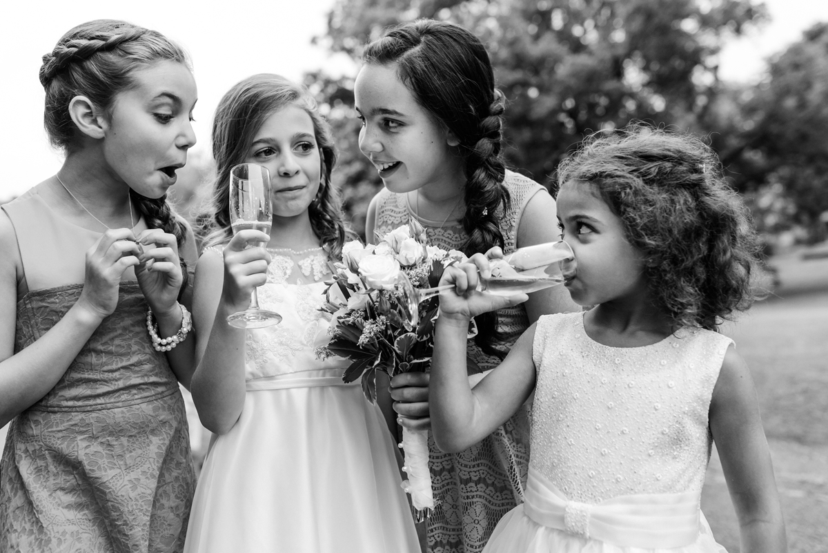 Candid photo of little girls at wedding, excited to be drinking bubbly in champagne glasses