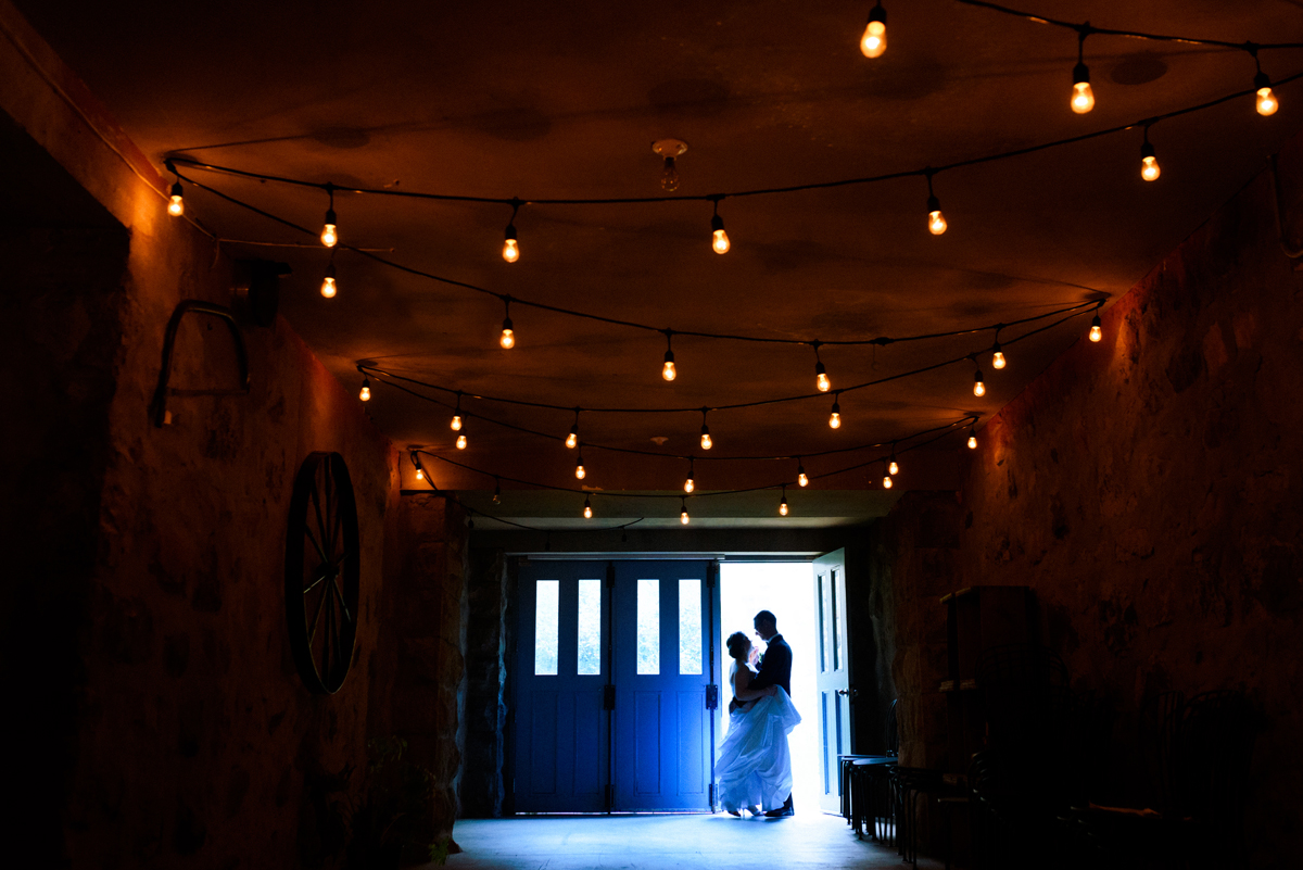 Creative portrait of wedding couple dancing in doorway of rustic hallway lit with hanging lights, at Abbaye d'Oka, Quebec
