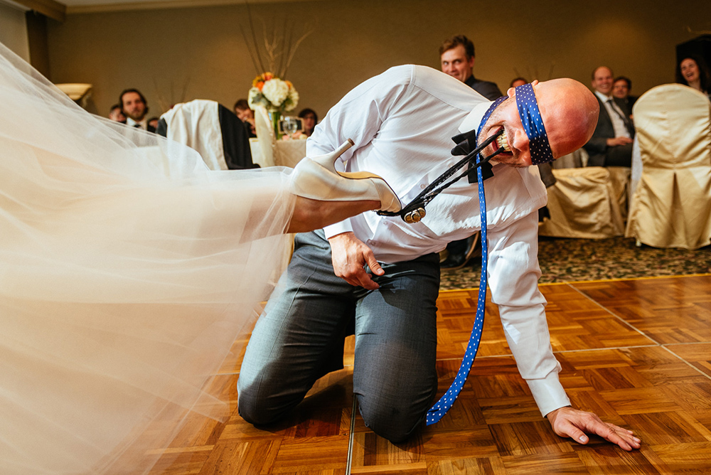 Groom removing garter with teeth
