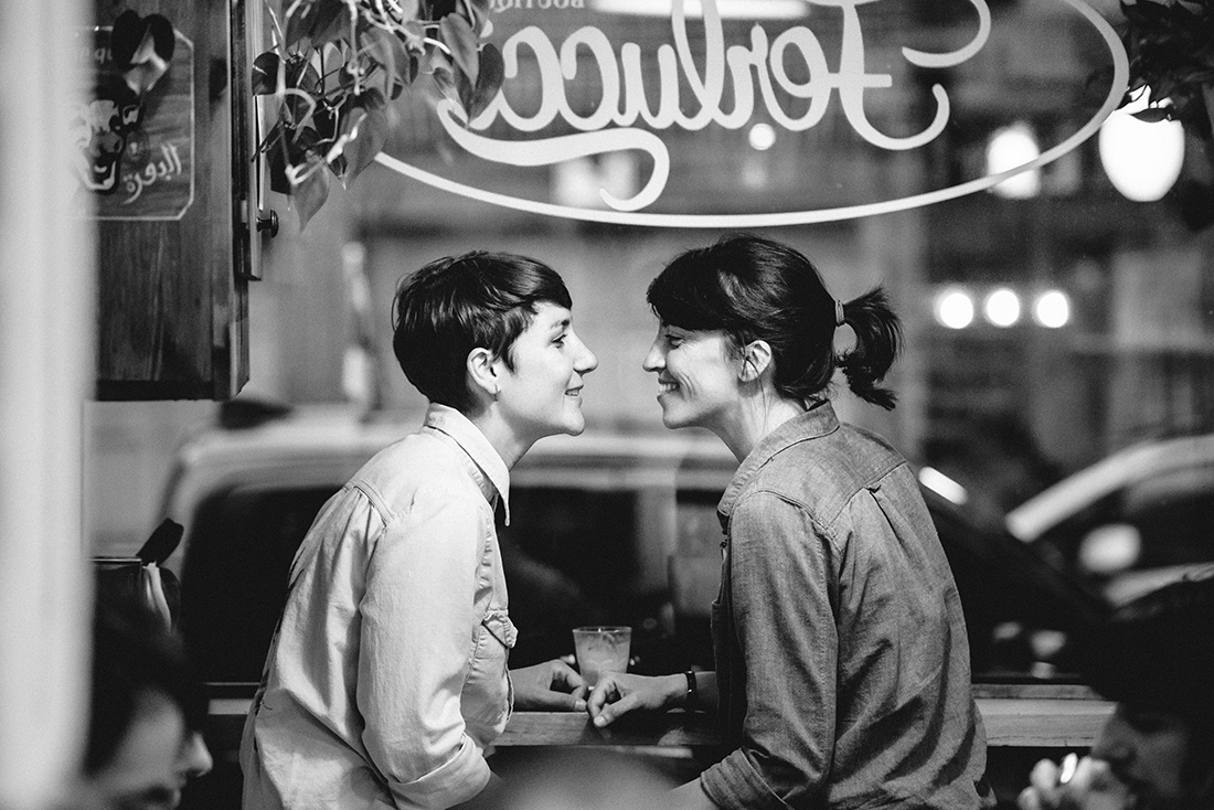 Queer engagement photo at Ferlucci Cafe in Montreal