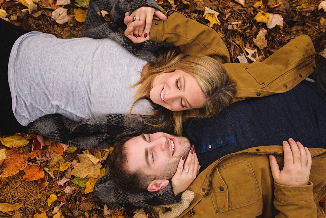 Engaged couple lying in the leaves for an autumn engagement photoshoot