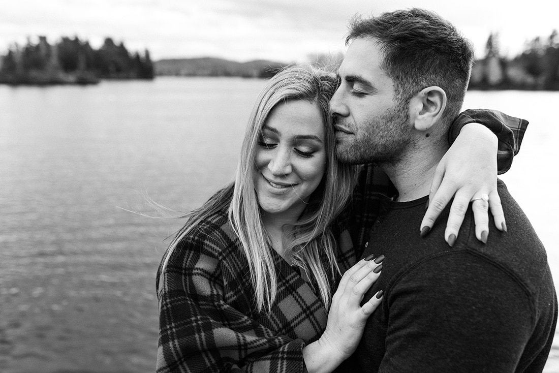 Black and white engagement photo by the lake