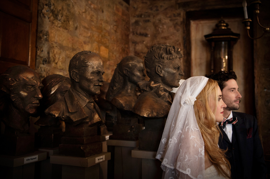 Wedding photo of bride and groom in room full of statues